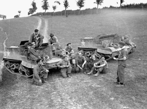 Lieutenant Stan Biggs briefing Universal Carrier flamethrower crews of The Queen's Own Rifles of Canada, Vaucelles, France, 29 July 1944. (L-R on ground): Corporal H.A. Campbell, Riflemen W.T. Orton, W.K. Cousineau, L.G. Jones, K. White, and Lieutenant Biggs. (L-R on Carrier): Riflemen H.H. Pennell, W. Starostic, C. Tippet, and Sergeant E. Rothwell.