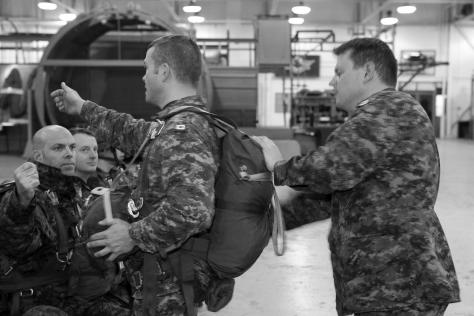 In his role as jumpmaster, Capt Scott Moody, Officer Commanding 60th Company, adjusts the equipment of Sgt Matt Kohler prior to a training session.